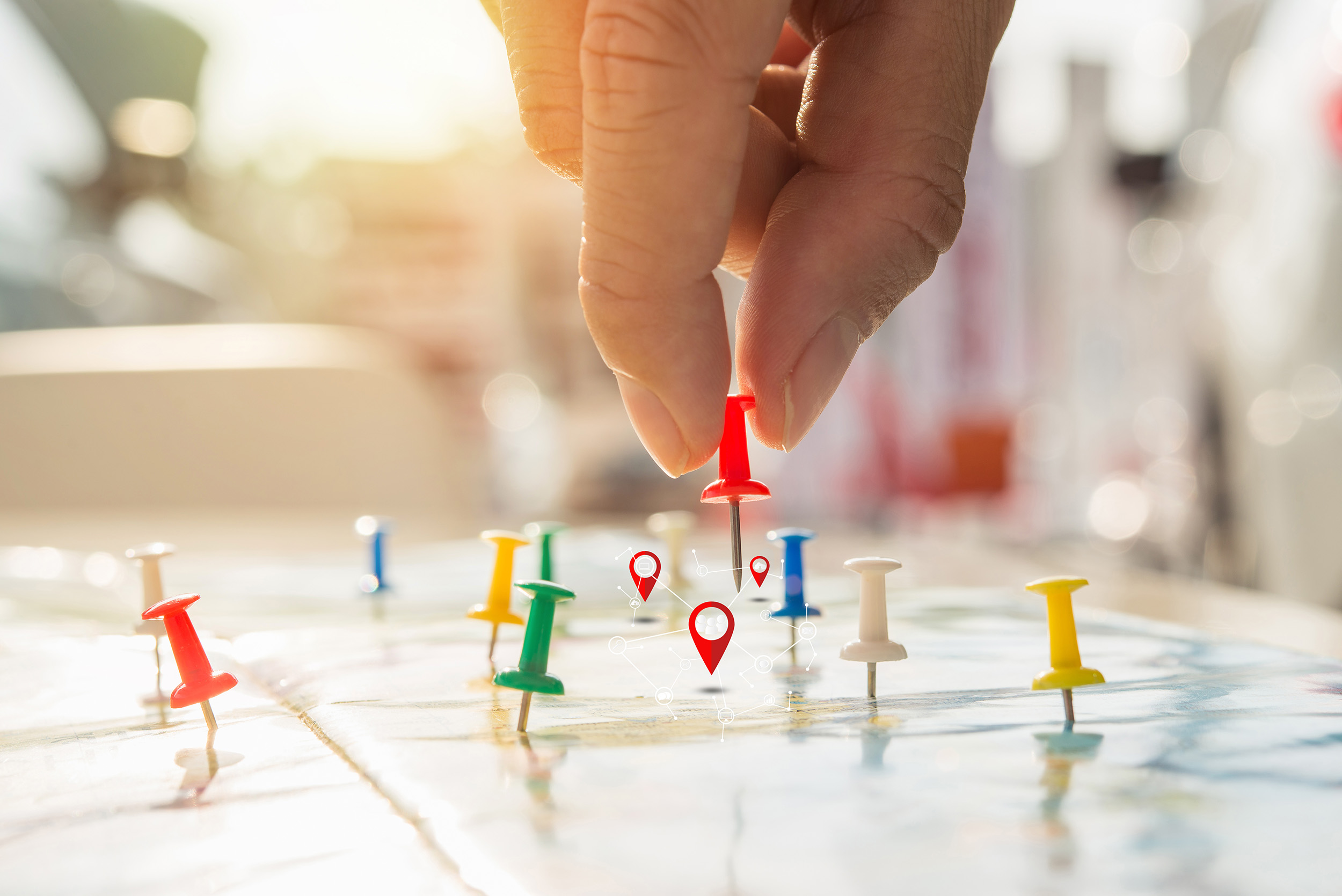 Soft Focus Hand Holding Paper Pin On Blur Perspective Road Map,